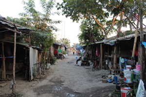 The main road through a worker camp in San Kham Pang district, Chiang Mai province. A car can fit down it, but it's tight.