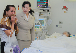 Paveena Hongsakul, centre, consoles Rattana Nakhonsopha, whose three-year-old daughter has become unconscious after she was left in a school van for seven hours.