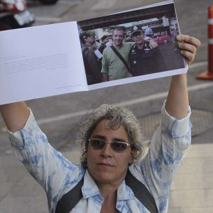 Elisabetta Polenghi, younger sister of shot Italian photographer Fabio Polenghi, holds up a book of his work outside a Thai court