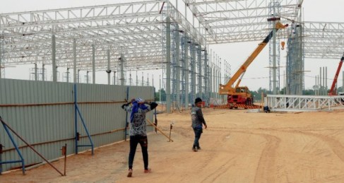 Workers walk at the 168 Platinum mall building site in Udon Thani in northeastern Thailand