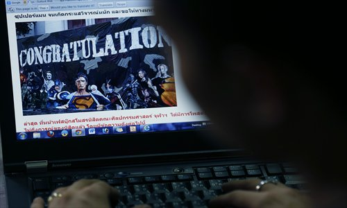 A Thai student looks at a website displaying a picture of a mural on campus depicting Adolf Hitler along with several comic book heroes inside, in Bangkok on July 16
