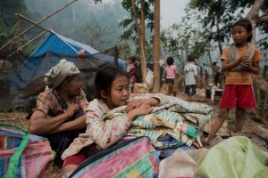 Myanmar refugees sit with their belongings as they start to build temporary shelters with bamboo and leaves at the Mae Surin camp in Mae Hong Son province, northern Thailand.