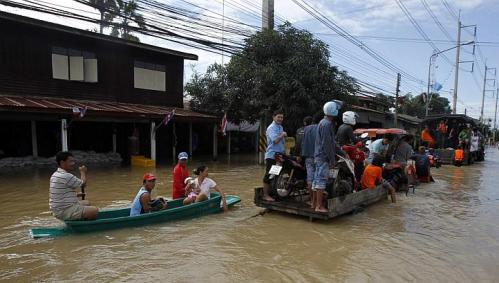 Residents sit on a loader and boat as it makes its way down a flooded street at Srimahaphot district in Prachin Buri province, east of Bangkok