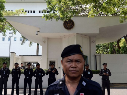 Thai policemen stand guard outside the US Embassy as anti-government protestors shout slogans during a protest march in Bangkok