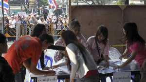 Anti-government protesters rally as officials work at a polling station in Bangkok in an attempt to derail a contentious general election scheduled for next week.
