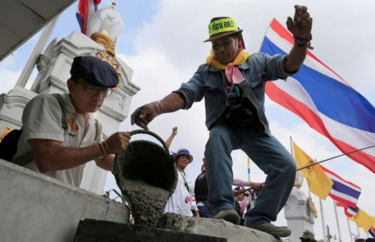 Anti-government protesters pour cement on concrete barriers to seal the gate of the prime minister's office of government house during a rally in Bangkok