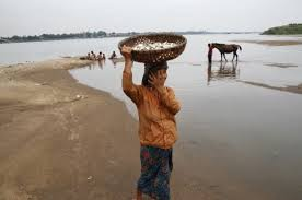 Chea Sophorn, 39, carries a fish basket at the Mekong River bank