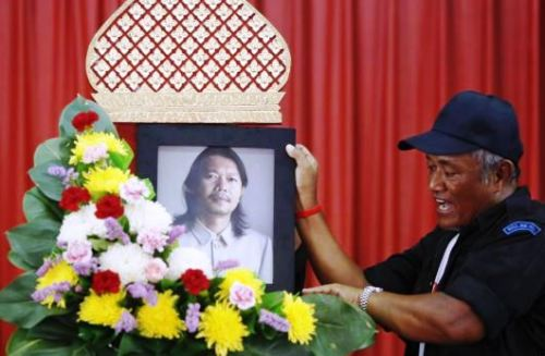 A man places a portrait of Kamol Duangphasuk, who was killed a day before, as his body is prepared for a funeral at a Buddhist temple in Bangkok