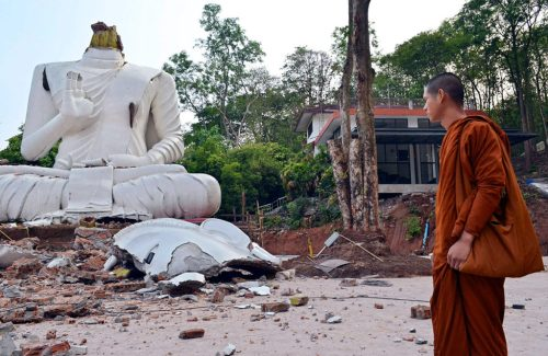A Thai Buddhist monk looks at a damaged Buddha statue caused by the 6.3 magnitude earthquake at Wat Udom Waree temple in Phan district, Chiang Rai province