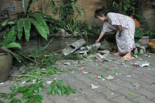 A woman picks up debris in her yard after the quake hit downtown Mae Sai district of Chiang Rai.