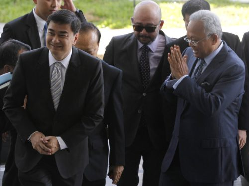 Former Thai Prime Minister Abhisit Vejjajiva, left, and his then deputy Suthep Thaugsuban arrive at the Department of Special Investigation in Bangkok