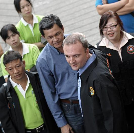 British activist Andy Hall (2nd R) is surrounded by supporters as he arrives for a hearing at a court in Bangkok on September 2, 2014 (AFP Photo/Christophe Archambault)