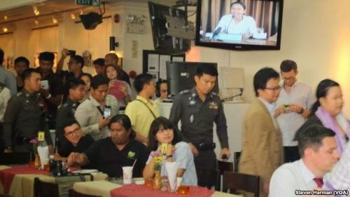 Police officers inside the Foreign Correspondents Club to deliver letters to human rights panelists. Photo Steve Herman