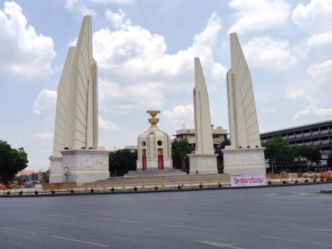 Bangkok's iconic Democracy Monument is currently fenced off. A large, hand-written sign reads 'closed for renovation'.