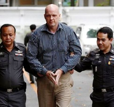 Police officers escort Thomas Andrew Erickson (C), a 47-year-old American, before a news conference at the Central Investigation Bureau in Bangkok