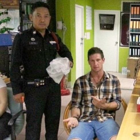 27-year-old Jacob Saveisberg was forced to pose with police officers after his arrest.