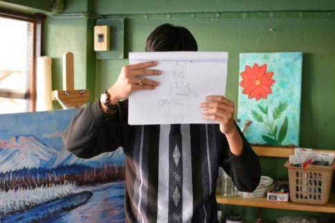 Saeng holds a picture he's drawn of a woman dressed in designer clothes © UNICEF EAPRO/2014/Andy Brown