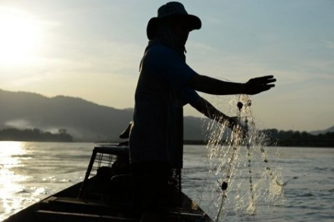 A fisherman stands on a boat as he lays his net in the Mekong river in Wiang Kaen, a district in the northern Thai province of Chiang Rai