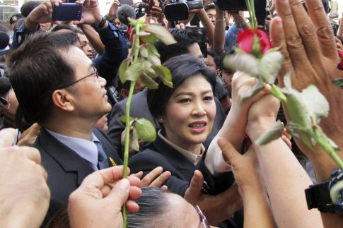 Ousted Thai leader Yingluck Shinawatra leaving court Tuesday through a sea of supporters after pleading not guilty to charges related to a botched rice-subsidy program