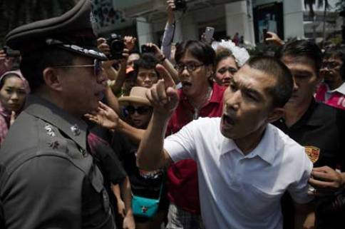 An anti coup protester shout at Thai soldiers (not seen) as a police officer (L) tries to calm him down during a planned gathering in Bangkok