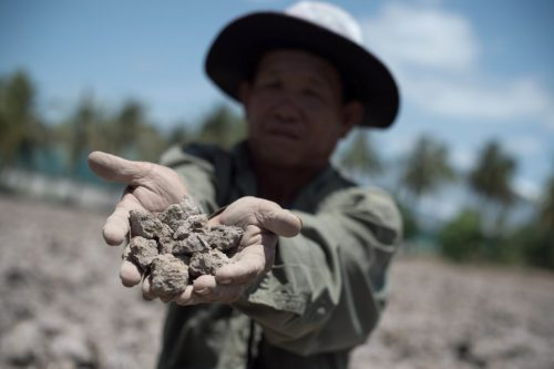 TO GO WITH Thailand-economy-rice-drought,FOCUS by Jerome Taylor This picture taken on July 2, 2015 shows a Thai farmer showing the dried out soil from his field which usually yields a crop, in Bang Pla Ma district, Suphanburi province, a two-hour drive north of Bangkok.  Thailand's vital rice belt is being battered by one of the worst droughts in living memory, forcing impoverished farmers deeper into debt and heaping fresh pain on an already weak economy -- seen as the junta's Achilles heel.     AFP PHOTO / Nicolas ASFOURI