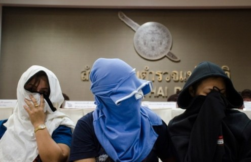 Unidentified suspects seated at press conference in Bangkok
