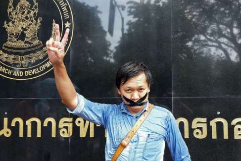 Thai journalist Pravit Rojanaphruk flashes a V-sign as he stands with his mouth taped outside a military base in Bangkok where he had been summoned by the junta