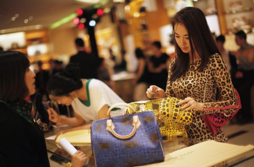 A woman shops in a Louis Vuitton store during Vogue's 4th Fashion's Night Out: Shopping Night with Celebrities in downtown Shanghai September 7, 2012. Louis Vuitton is courting China's wealthy with one-of-a-kind shoes and bags it is branding as unique works of art to reclaim its exclusive cachet in the luxury market. REUTERS/ Carlos Barria  (CHINA - Tags: FASHION BUSINESS SOCIETY WEALTH) - RTR37MTH