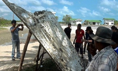 Thai people look at a large chunk of metal found on a beach in Nakhon Si Thammarat province, Thailand