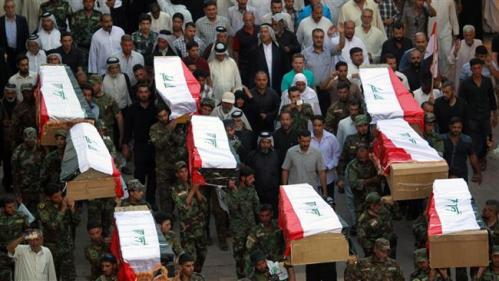 Iraqi soldiers carry coffins containing the remains of ten of their comrades who were killed in the Speicher massacre.