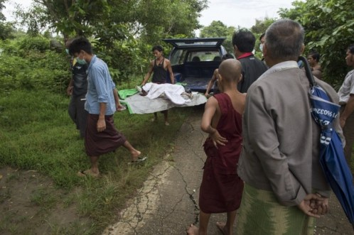 Hospital workers carry the body of three-year-old Nay La Linn, a victim of an exorcism ritual, for burial at a public cemetrey in Twante town, south of Yangon - Photo AFP