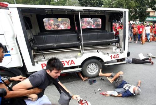 Protesters lie on the ground after being hit by a police van during a rally in front of the US embassy in Manila. - Getty Image