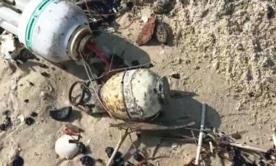 hand grenade found among the tar balls
