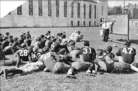 University of Chicago football coach Amos Alonzo Stagg explains plays to his team on a field next to the Henry Crown Field House, Chicago, September 16, 1932. CHM, ICHi-051374
