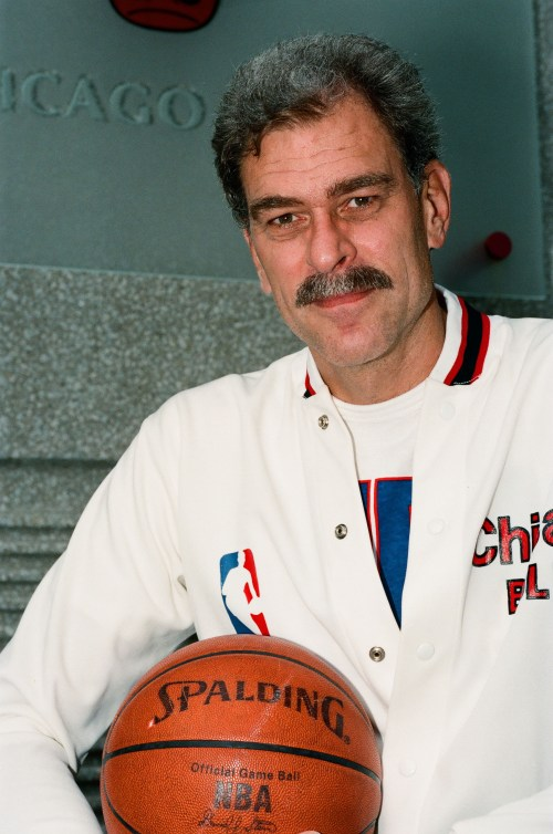 Seated portrait of Phil Jackson holding a basketball