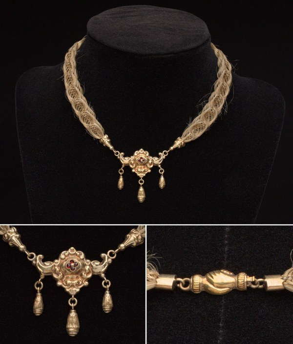 Necklace made with woven human hair and a gold pendant with garnet embellishments; image includes closeup of gold pendant and necklace clasp in the shape of two holding hands