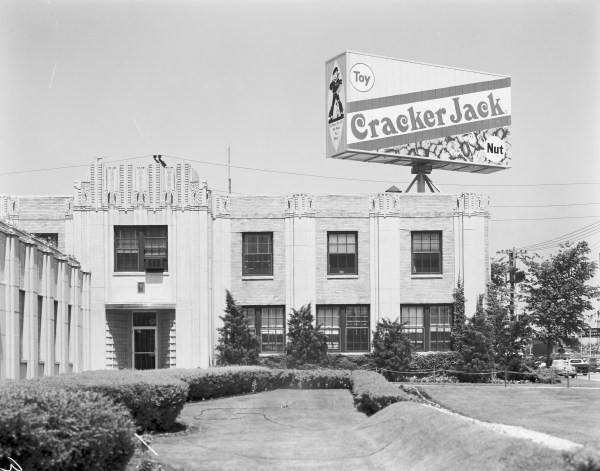 Black and white photograph of exterior of Cracker Jack plant with billboard