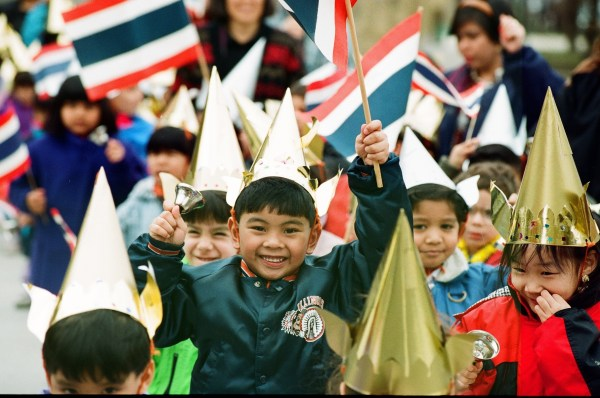 Children march in parade waving the Thai flag to celebrate Thai New Year at Albany Park