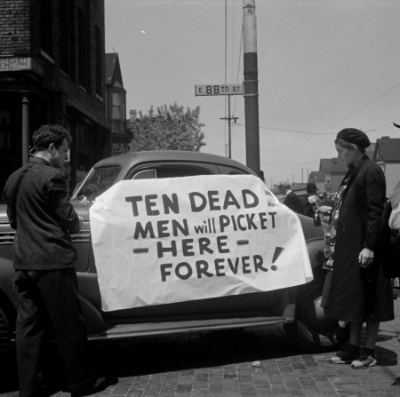 A woman and a man, who is possibly a photographer, looking at a sign on an automobile at the Republic Steel strike in Chicago, Illinois, 1937. One of a set of images showing police officers, politicians, and other people doing activities related to the strike.