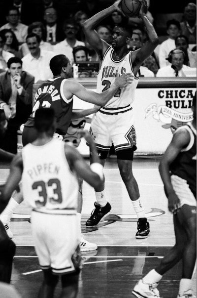 In the middle of a game Bill Cartwright is guarded with the ball looking to pass