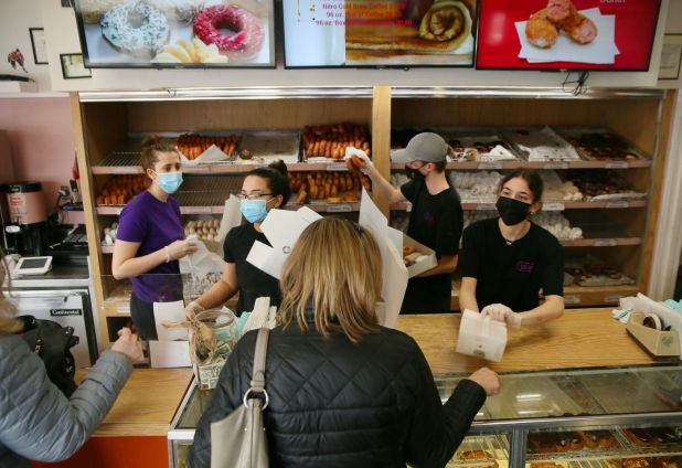 Spunky Dunkers workers from left: Maggie O'Brien, Michelle Hanrahan, Brenday Rolloff, and Ilianna Giannakouras rush to fill donut orders at Spunky Dunkers on February 21, 2021 in Palatine.