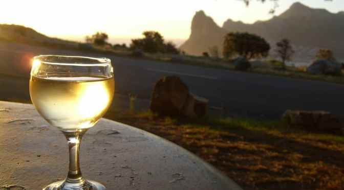 A glass of white wine on a table with mountains for a backdrop