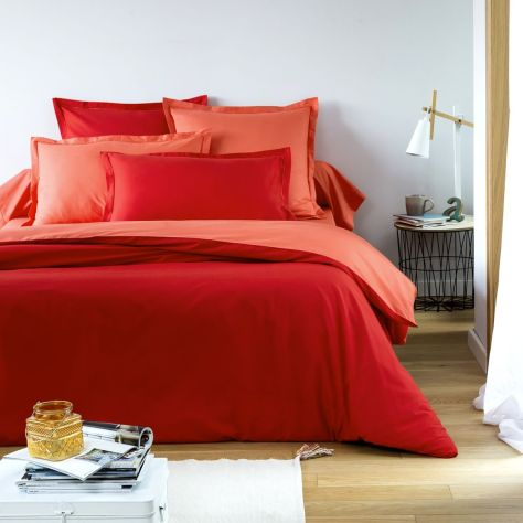 A bed made up in red tones