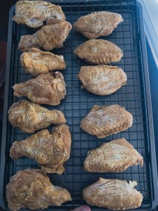 Seasoned party cut chicken wings on a cooling rack before resting in the fridge.