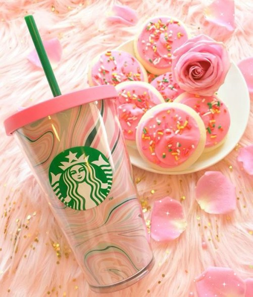 A pink Starbucks tumbler on a pink rug with a pink rose.