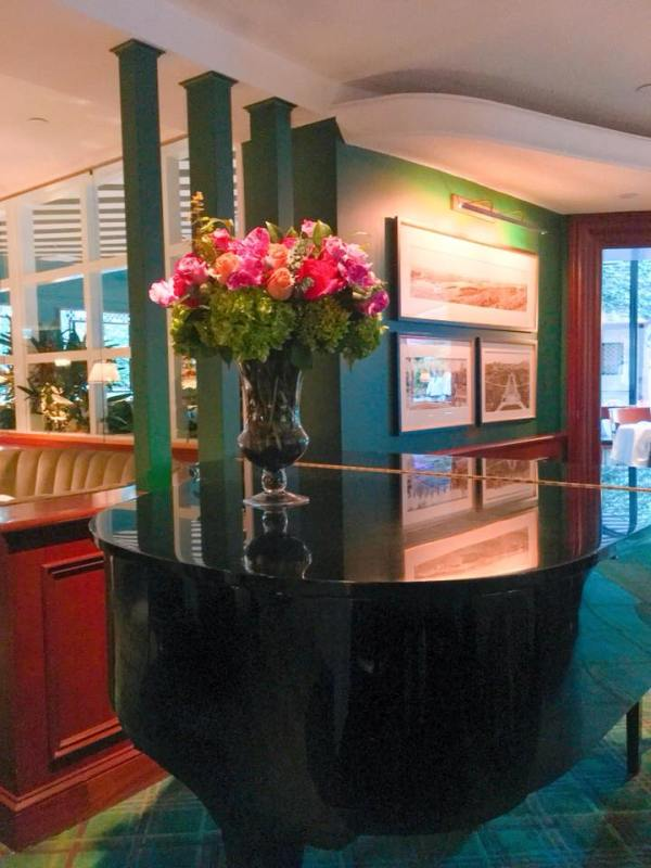 The piano inside the Polo Lounge with a bouquet of flowers on top