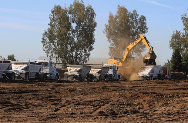 A line of trucks waits to be filled at the Glenn-Colusa Irrigation District pumping plant north of Hamilton City. The soil, left over from the digging of the Glenn-Colusa Canal, is being used to build a replacement for the J Levee that protects the town from the Sacramento River. (Steve Schoonover --Enterprise-Record)
