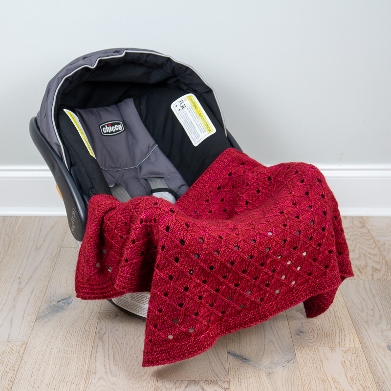 Dark pink DK weight KiYO blanket on car seat