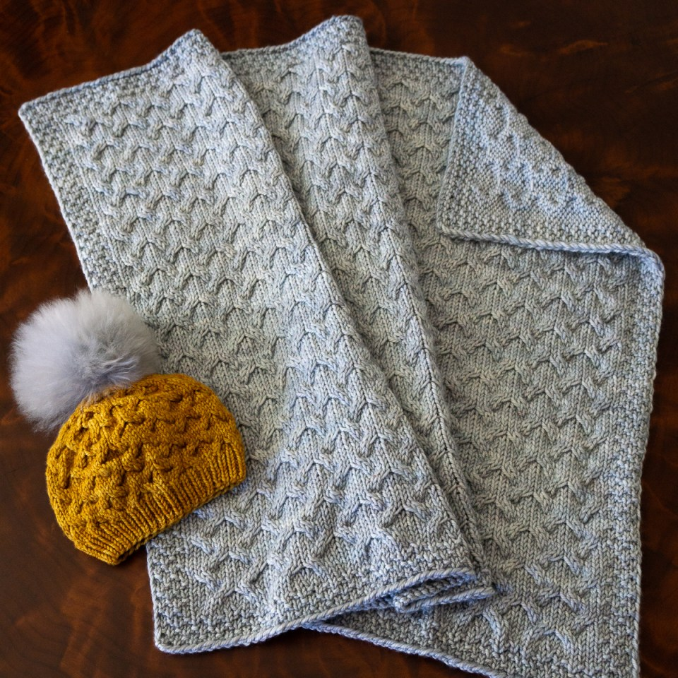 A light blue Astrophil Blanket with matching yellow Astrophil Hat.