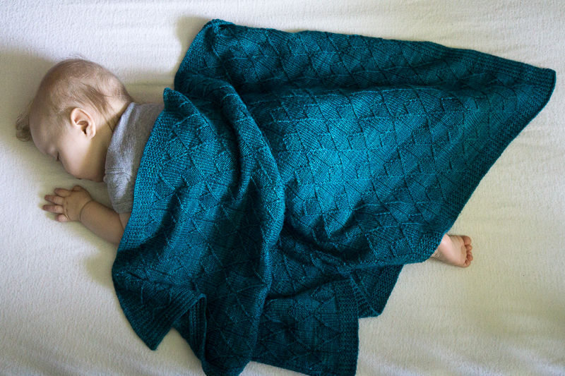 An ocean-blue Sérac Blanket covering a sleeping infant.